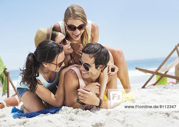 Glückliche Freunde  die am Strand übereinander liegen.