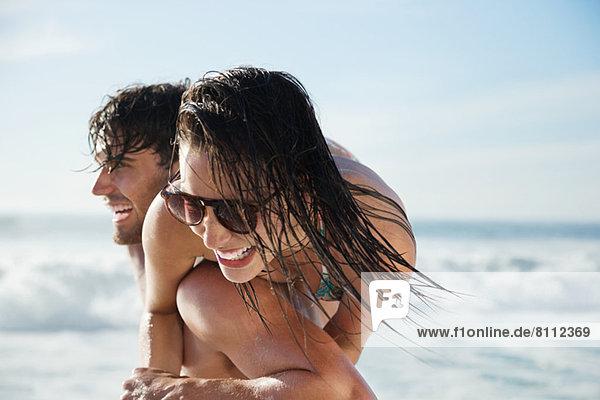 Mann mit begeisterter Frau am Strand