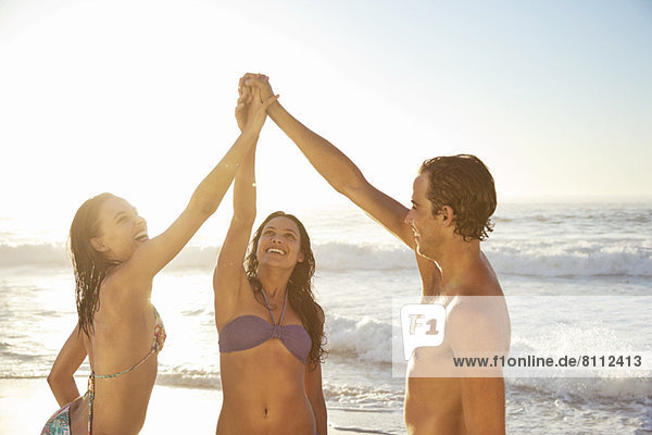 Freunde High Fiving am Strand