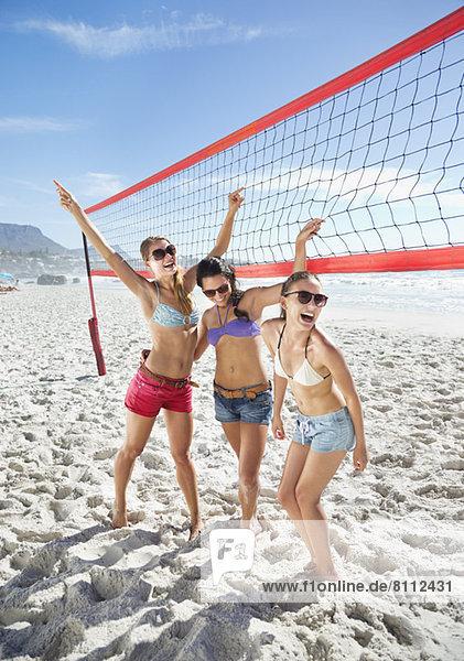 Glückliche Freunde auf dem Beachvolleyballplatz