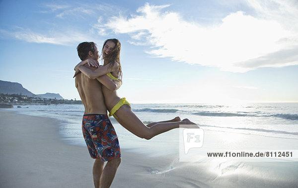 Ein glückliches Paar umarmt sich und dreht sich am Strand.