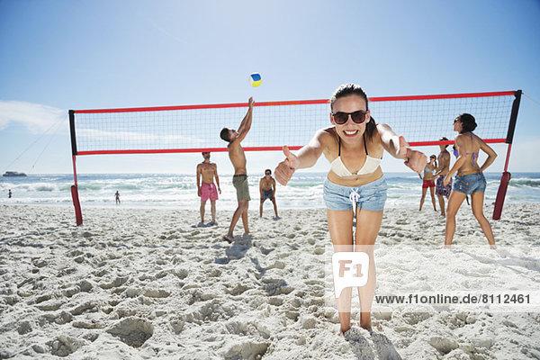 Porträt einer selbstbewussten Frau  die auf dem Beachvolleyballfeld die Daumen hochzieht