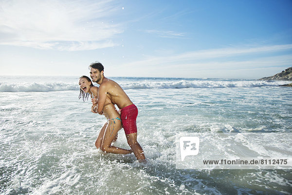 Enthusiastisches Paar  das sich umarmt und im Meer plätschert.