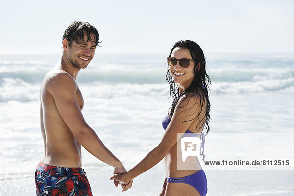 Portrait of happy couple holding hands on beach