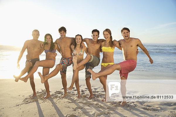 Portrait von lächelnden Freunden  die sich am Strand umarmen und treten.