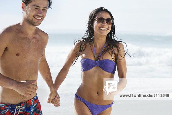 Ein glückliches Paar  das Händchen hält und am Strand rennt.