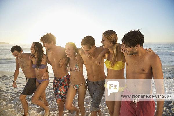 Freunde in Bikinis und Badehosen umarmen und am Strand spazieren gehen