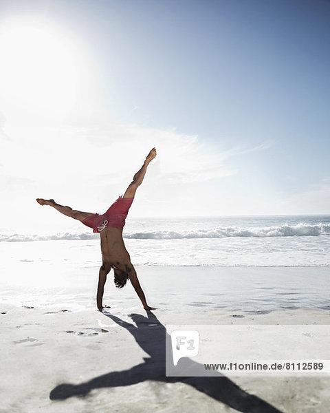 Mann in Badehose beim Handstand am Strand
