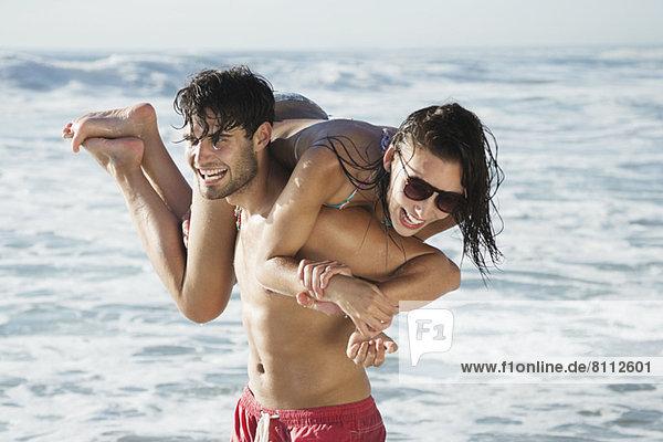 Glücklicher Mann mit Frau am Strand