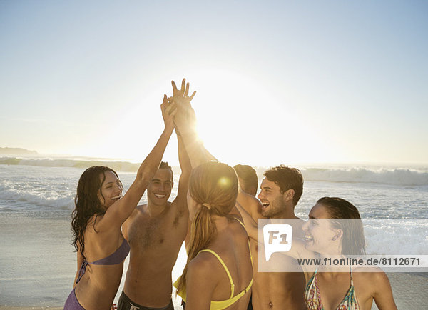 Freunde hoch fiving in Huddle am Strand