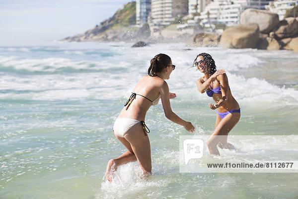 Verspielte Freunde in Bikinis beim Plantschen im Meer