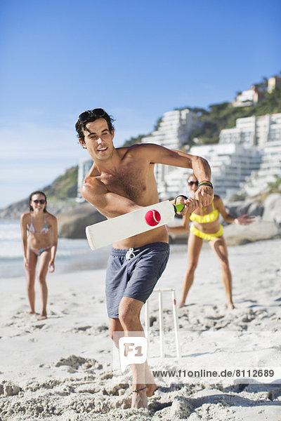 Mann spielt Cricket am Strand
