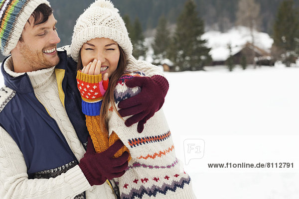 Couple laughing and hugging in snowy field