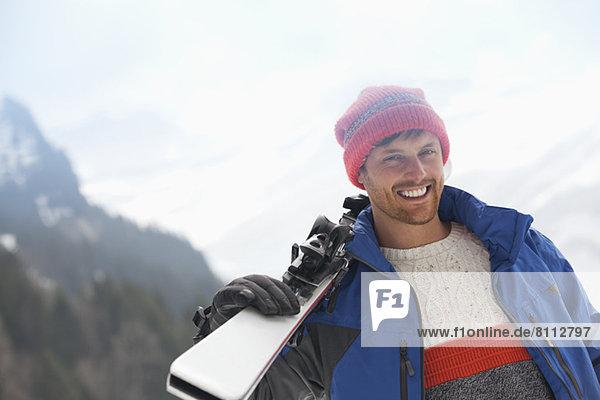 Porträt eines lächelnden Mannes mit Skiern