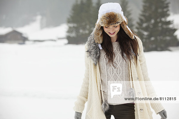 Smiling woman wearing fur hat in snowy field