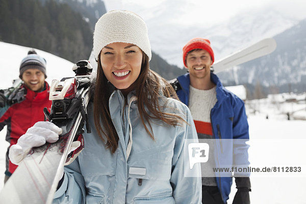 Portrait of smiling friends carrying skis