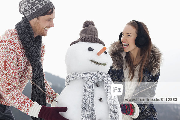 Happy couple making snowman