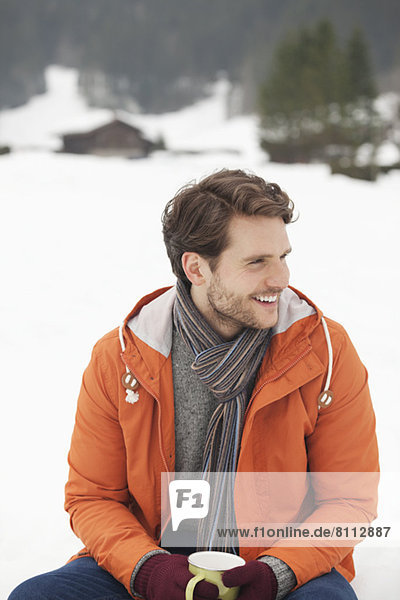 Smiling man drinking coffee in snowy field