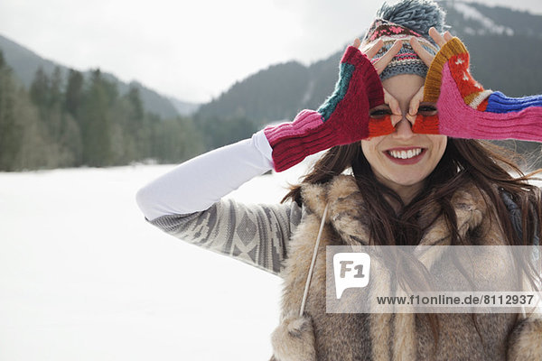 Portrait of smiling woman circling eyes with fingers in snowy field