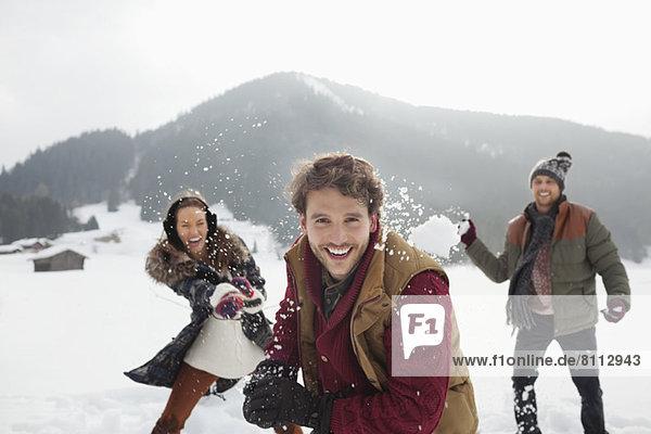 Porträt von verspielten Freunden  die Schneebälle ins Feld werfen