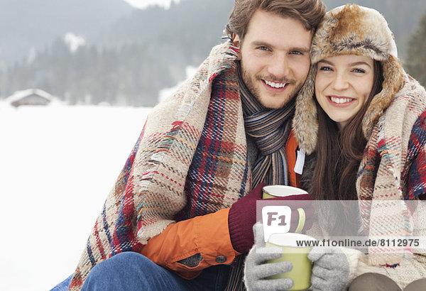 Portrait of happy couple drinking coffee in snowy field
