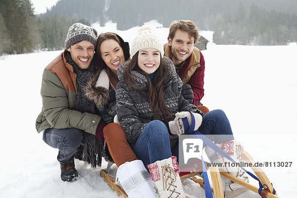 Portrait of happy friends on sled in snowy field