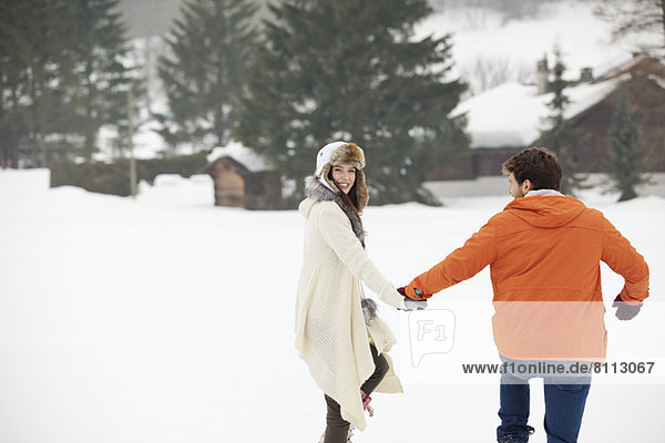 Happy couple holding hands and walking in snowy field