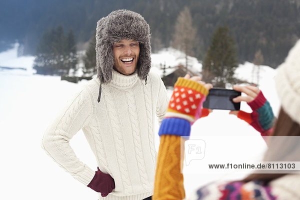 Woman photographing man in fur hat in snowy field
