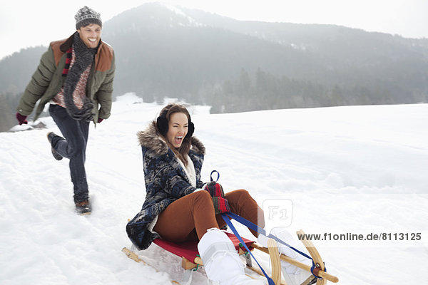 Enthusiastic couple sledding in snowy field