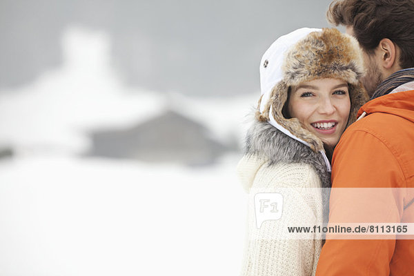 Portrait of smiling woman hugging man in snowy field