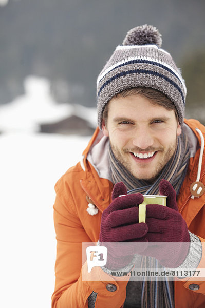 Close up portrait of smiling man in knit hat and gloves drinking coffee in snowy field