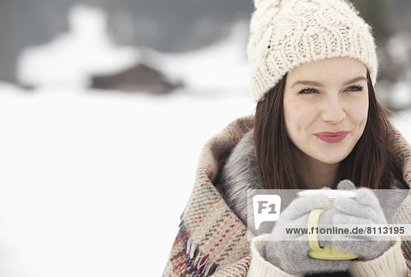 Close up of smiling woman in knit hat and gloves drinking coffee in snowy field