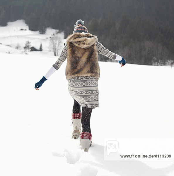 Woman walking in snowy field