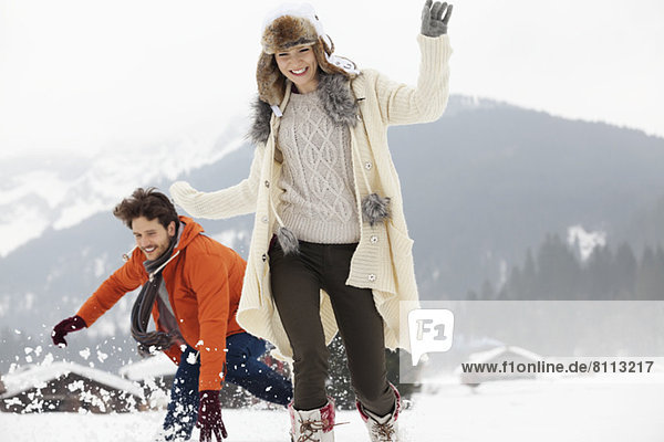 Playful couple running in snowy field