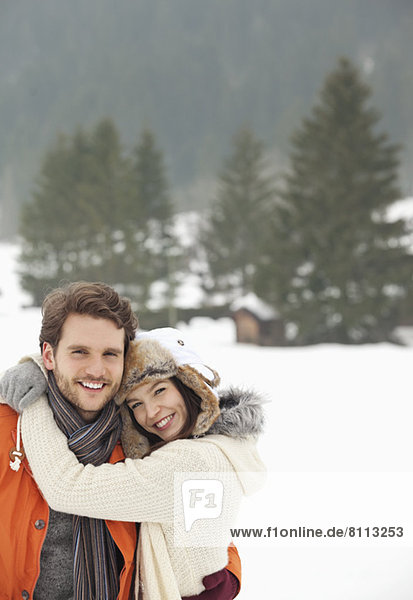 Portrait of smiling couple hugging in snowy field
