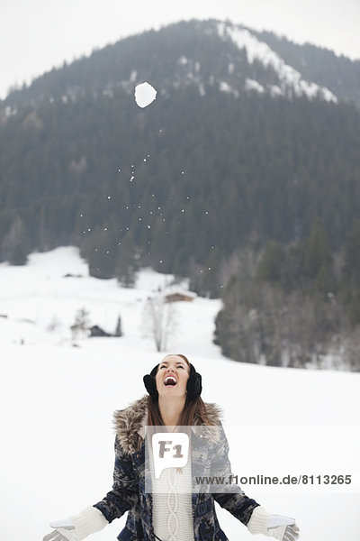 Snowball falling above enthusiastic woman in field