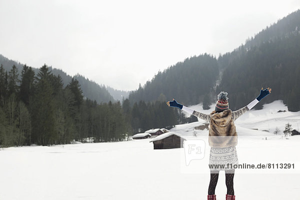 Carefree woman with arms outstretched in snowy field