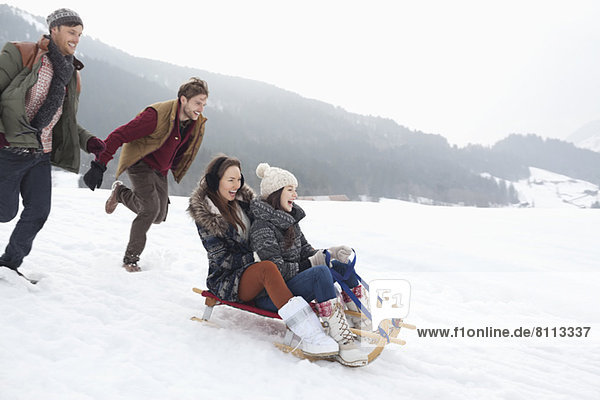 Enthusiastic friends sledding in snowy field