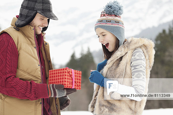 Man surprising woman with gift in snowy field