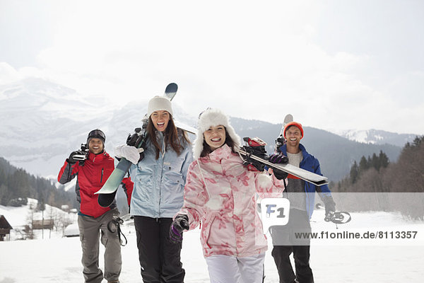 Begeisterte Freunde mit Skiern im Schneefeld