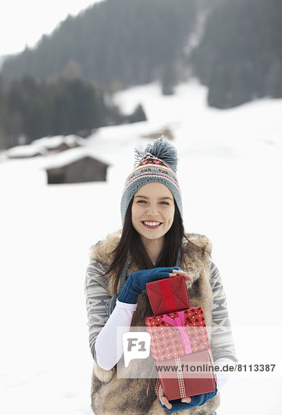 Portrait of smiling woman holding Christmas gifts in snowy field