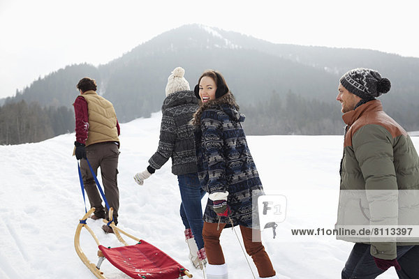Happy friends pulling sleds in snowy field
