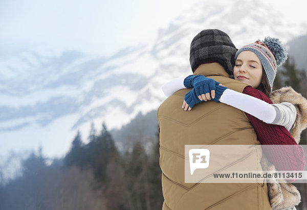 Serene couple hugging with mountains in background