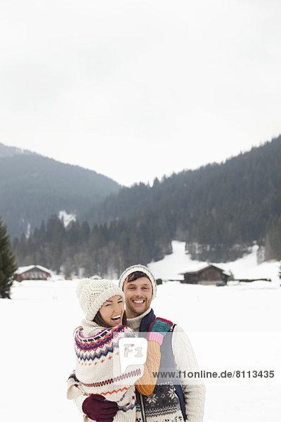 Portrait of happy couple hugging in snowy field