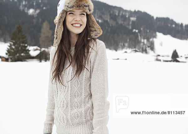 Happy woman wearing fur hat in snowy field