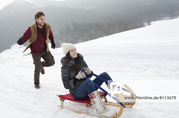 Happy couple sledding in snowy field
