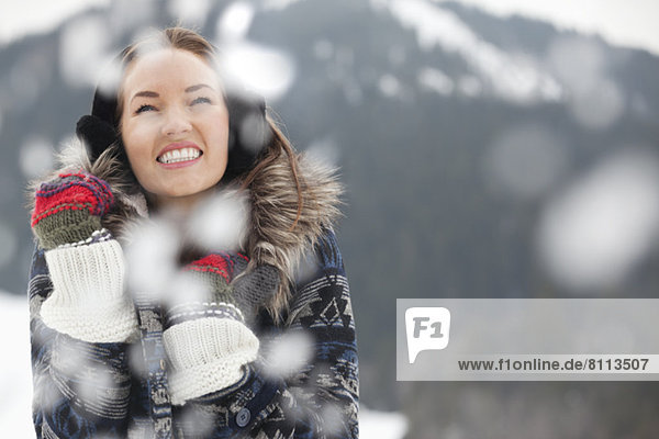 Happy woman wearing ear muffs and gloves in snow