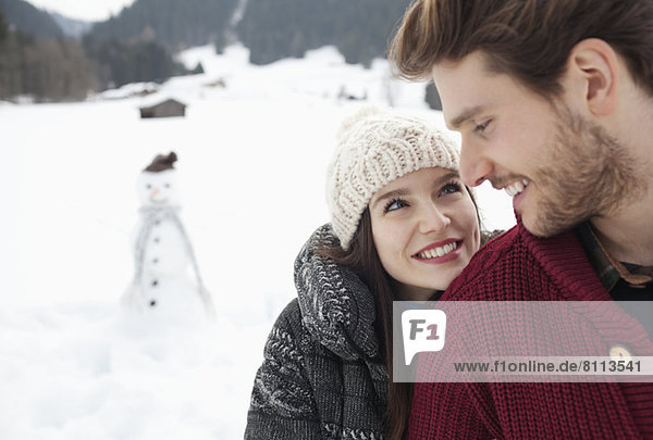 Close up of happy couple in snowy field with snowman