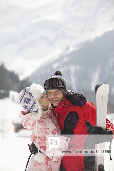 Happy couple with skis kissing in snowy field
