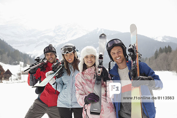 Portrait of smiling friends with skis in snowy field